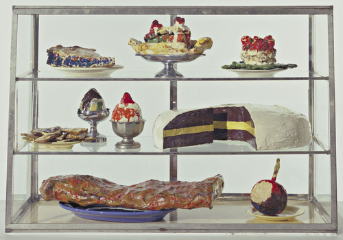 Claes Oldburg, Pastry Case I, 1962. Burlap and muslin soaked in plaster, painted with enamel, metal bowls, and ceramic plates in glass-and-metal case, 52.7 x 76.5 x 37.3 cm, The Museum of Modern Art, New York.